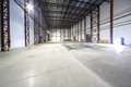 Large light empty hangar with concrete floor and entrances for trucks Stock Photos