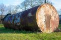 Large metal barrel metalyva big old out the door and covered with rust Stock Photo