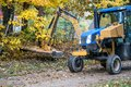 A large mower cuts back high grass along the road Royalty Free Stock Photo