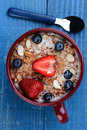 Large mug with healthy cereal high angle photo of a filled a whole grain and fruit strawberries blueberries and sliced almonds on Royalty Free Stock Image