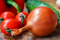 Large onion, cherry tomatoes, sweet peppers and cucumbers on a old wooden table Royalty Free Stock Photo