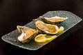 Large oysters with lemon zest on platter shelled a and slices Stock Image
