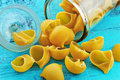 Large pasta shells in a glass jar on blue background