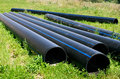 Large plastic pipes lie in the green grass Royalty Free Stock Photo