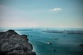 Large rock overlooking harbour with bridge Royalty Free Stock Photo