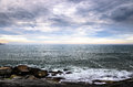 Large rocks, many clouds, and the horizon on a seascape Royalty Free Stock Photo