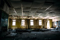 Large ruined room with windows, control center room in abandoned factory Royalty Free Stock Photo
