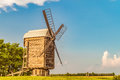 Large Russian wooden windmill on a background of green trees