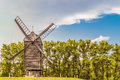 Large Russian wooden windmill on a background of green trees Royalty Free Stock Photo