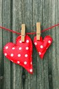 Large small red heart shape white spots pegged to washing line wooden grainy background Stock Photos