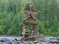 Large stacked stones inuksuk cairn trail marker rocks and balanced to form an stone landmark or as a or monument in front of Royalty Free Stock Photos