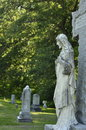 Large stone jesus christ statue with cross engraved in the forefront of cemetery Stock Photography