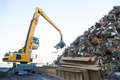 Large tracked excavator working a steel pile at a metal recycle yard Royalty Free Stock Image