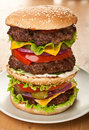 Large triple cheeseburger giant huge tasty on a plate Royalty Free Stock Photography