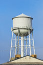 Large water tower sits behind a building Stock Images