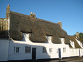 Large white house in england with a thatched roof Royalty Free Stock Photos
