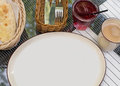 Large white plate. Bright bokeh background. Basket with Cutlery, white napkins, coffee Cup, sugar bowl, bread, wicker chairs. Dess Royalty Free Stock Photo