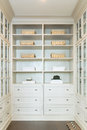 Large white walk-in closet with shelves Royalty Free Stock Photo