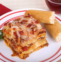 Lasagna dinner portion of and bread sticks on a plate Stock Image