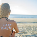 Last minute girl written with sunscreen on back of attractive woman sitting on beach looking at ocean Stock Images