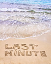 Last minute written on sand with waves in background vacation concept Royalty Free Stock Photos