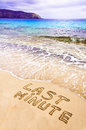 Last minute written on sand with waves in background vacation concept Stock Photo