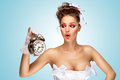 She is always late a beautiful vintage pin up girl in a white wedding dress being in the morning and holding a retro alarm clock Stock Photo