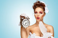 She is always late a beautiful vintage pin up girl in a white wedding dress being in the morning and holding a retro alarm clock Stock Image