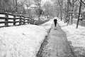 Late march snow storm black and white photo of person walking on a sidewalk next to rosedale estate in northwest washington dc in Stock Photography