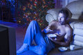 Late night tv shirtless caucasian man in pajamas sits on floor of living room watching and snacking at with christmas tree in Stock Photos