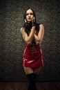 Latex doll seductive mistress in red dress posing in a dark room Royalty Free Stock Image