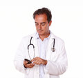 Latin doctor texting on his cellphone a portrait of a standing and a message using isolated studio Royalty Free Stock Photo