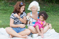Latin grandma mother and daughter camping on a park happy family including grandmother small dog Stock Photography