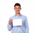 Latin man holding white blank card a portrait of a young on blue shirt a while smiling to people on isolated background copyspace Royalty Free Stock Photos