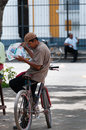 Latin man sitting on bike reading newspaper Royalty Free Stock Photo