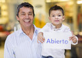 Latin men with his son holding an open sign Royalty Free Stock Photos