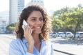 Latin woman with blue blouse listening at phone in the city Royalty Free Stock Photo