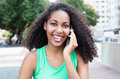 Latin woman with curly hair and green shirt at phone in city Royalty Free Stock Photo