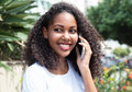 Latin woman with curly hair at phone in a park Royalty Free Stock Photo