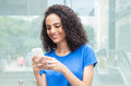 Latin woman with curly hair typing message at phone in city Royalty Free Stock Photos