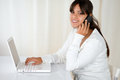 Latin woman using her laptop speaking on cellphone portrait of a young while is and looking at you copyspace Stock Photos