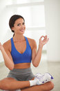 Latin woman in yoga class looking at you sitting and gym Royalty Free Stock Images