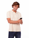 Latin young man in jeans reading on cellphone portrait of white background Stock Photo