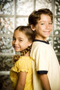 Latino brother and sister standing back to back Royalty Free Stock Photo