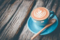 Latte art, Blue coffee cup on wooden background Royalty Free Stock Photo