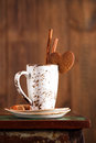 Latte coffee cup and heart cookie cinnamon sticks sugar on wooden table stool on brown wood background Stock Photography