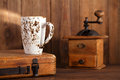 Latte coffee cup with nostalgic coffee grinder on background and old wood Stock Photo