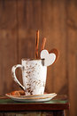 Latte coffee cup and sugar white heart cinnamon sticks on wooden table stool on brown wood background Stock Images