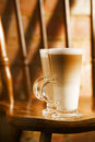 Latte coffee in tall glasses on vintage chair with old brick wal Royalty Free Stock Photo