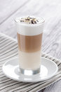 Latte macchiato sweet coffee with milk served in glass decorated with pinch of cacao and almonds flakes Royalty Free Stock Photo